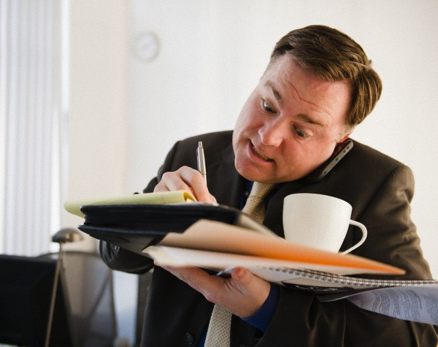 Businessman writing and talking on phone