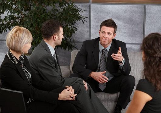 Businesspeople sitting on sofa, talking